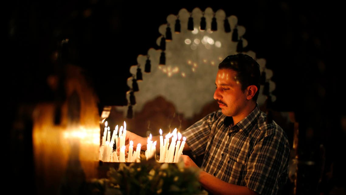 A Palestinian Orthodox Christian lights candles as he takes part in the Christian Orthodox Holy Fire ceremony at the Saint Porfirios church in Gaza City May 4, 2013. reuters