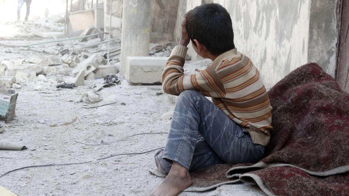 A Syrian child reacts following an air strike attack by government forces on the northern Syrian city of Aleppo on February 22, 2014.