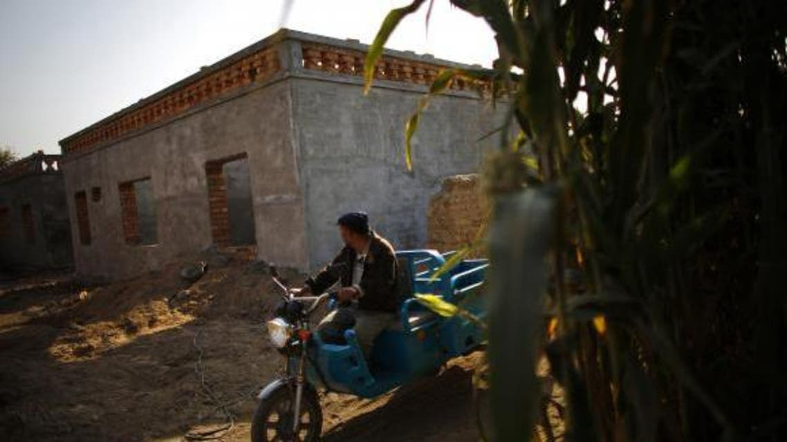 An ethnic Uighur man drives a tricycle near a construction site for new houses in Turpan, Xinjiang province Oct. 31, 2013. (Reuters)