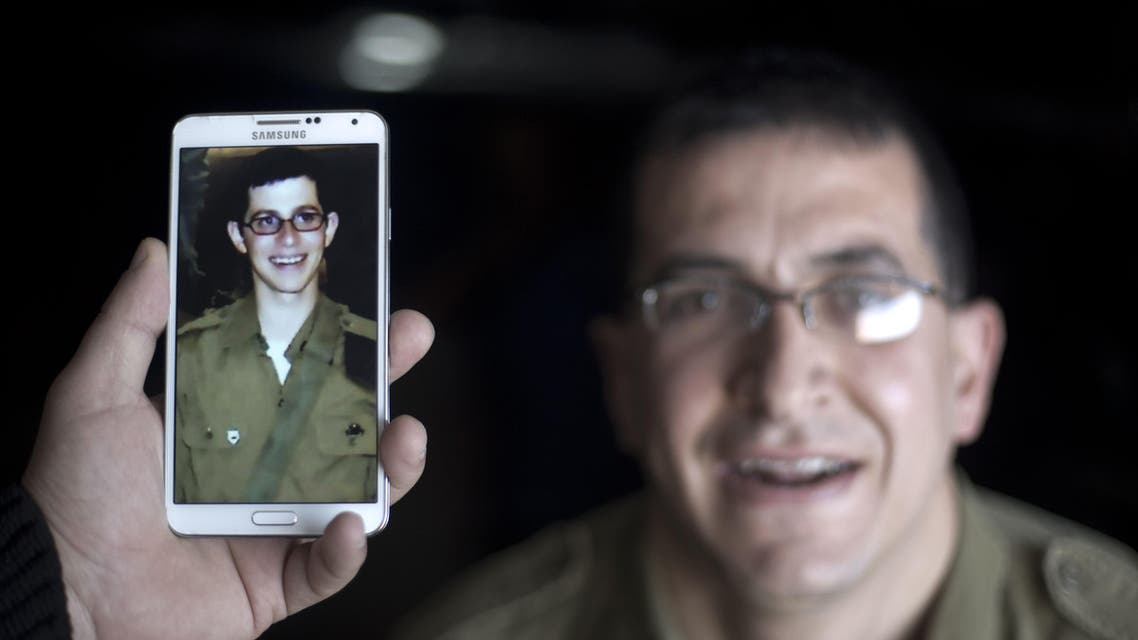 "A staff holds a mobile phone to compare the image of Gilad Shalit to the likeness of actor Mahmoud Karira (background) during the shooting of a 90-minute film entitled ""Fleeting Illusion"" on February 27, 2014 in Gaza City. afp"
