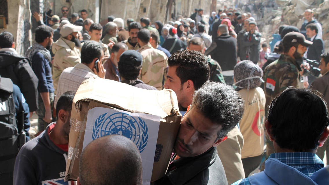 Residents of Syria's besieged Yarmuk Palestinian refugee camp, south of Damascus, receiving food parcels from the U.N. agency on Feb. 24, 2014. (AFP)