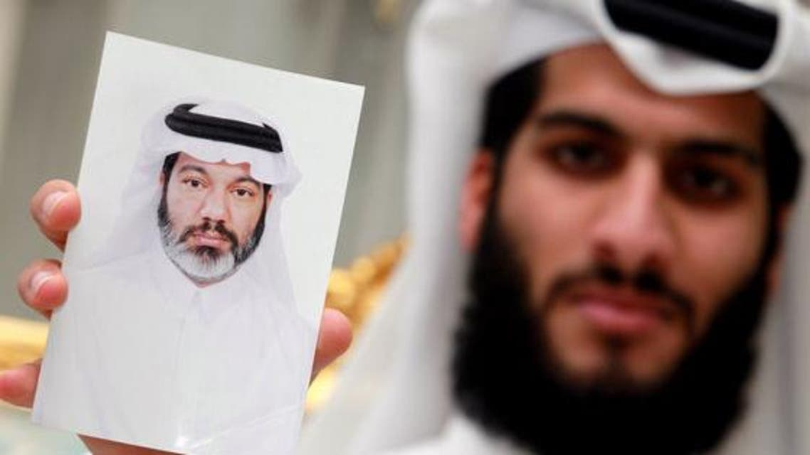 In this Sunday Sept. 8, 2013 file photo, Hasan al-Jidah holds a photograph of his father, detained Qatari doctor Mahmoud al- Jidah, at the family's home in Doha, Qatar. (Courtesy Photo of AP)