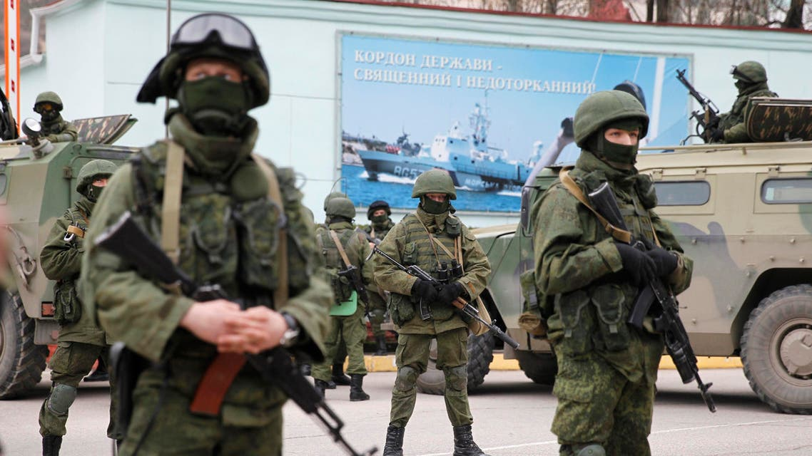 Armed servicemen wait near Russian army vehicles outside a Ukrainian border guard post in the Crimean town of Balaclava on March 1. (Reuters)