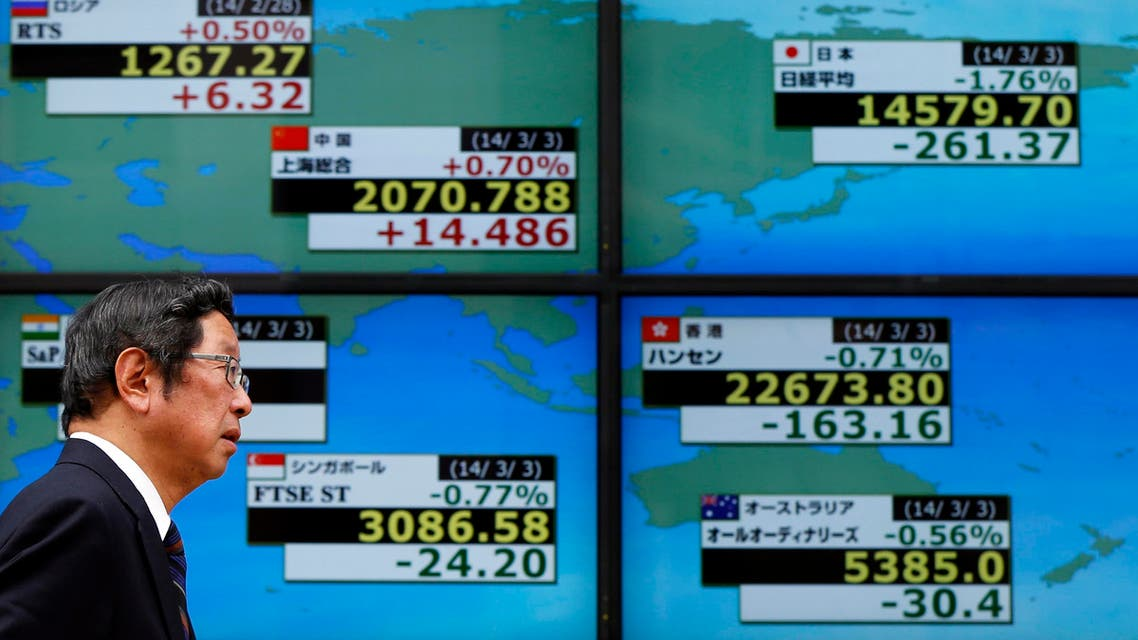 A man walks past an electronic board showing stock prices outside a brokerage in Tokyo on March 3, 2014. (Reuters)