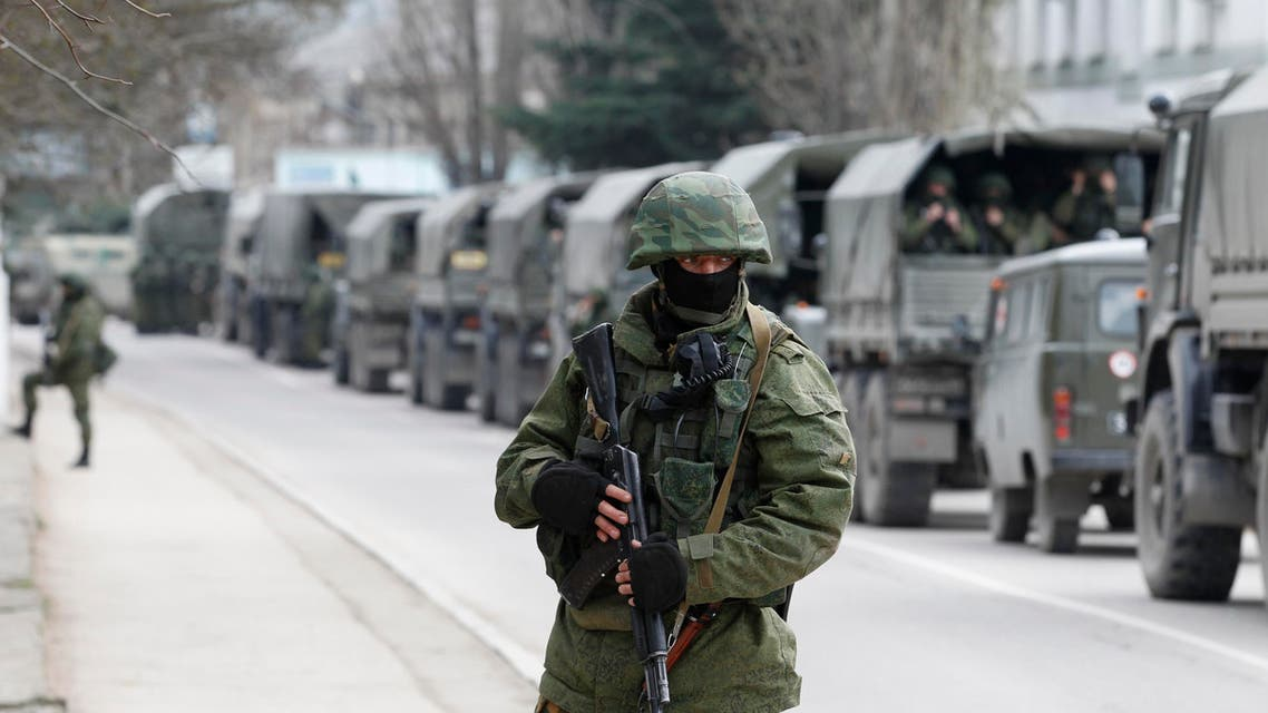 Armed servicemen wait in Russian army vehicles outside a Ukrainian border guard post in the Crimean town of Balaclava on March 1. (Reuters)