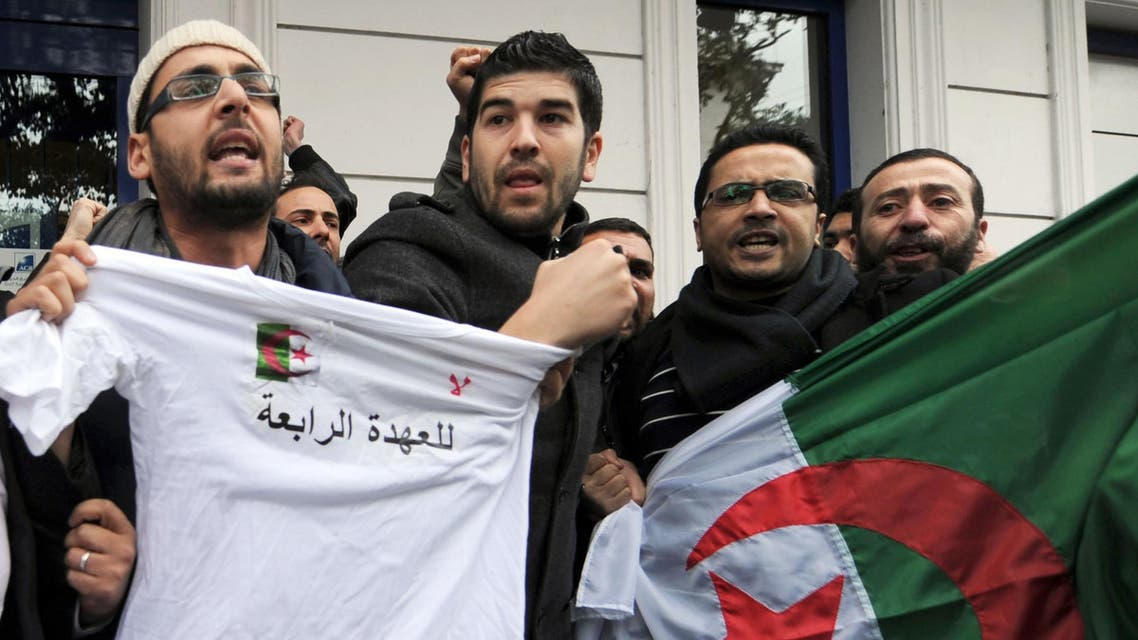 """Algerian demonstrators hold their national flag and a t-shirt reading in Arabic: """"No to a fourth term"""" during a protest against Algerian President Abdelaziz Bouteflika. (AFP)"""