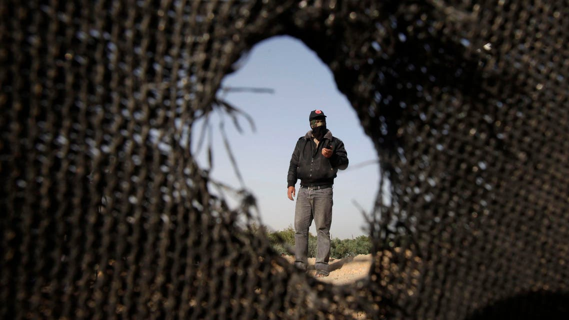 A Palestinian militant of the Democratic Front for the Liberation of Palestine (DFLP) inspects a training base after it was hit by an Israeli air strike in Rafah in the southern Gaza Strip April 28, 2013