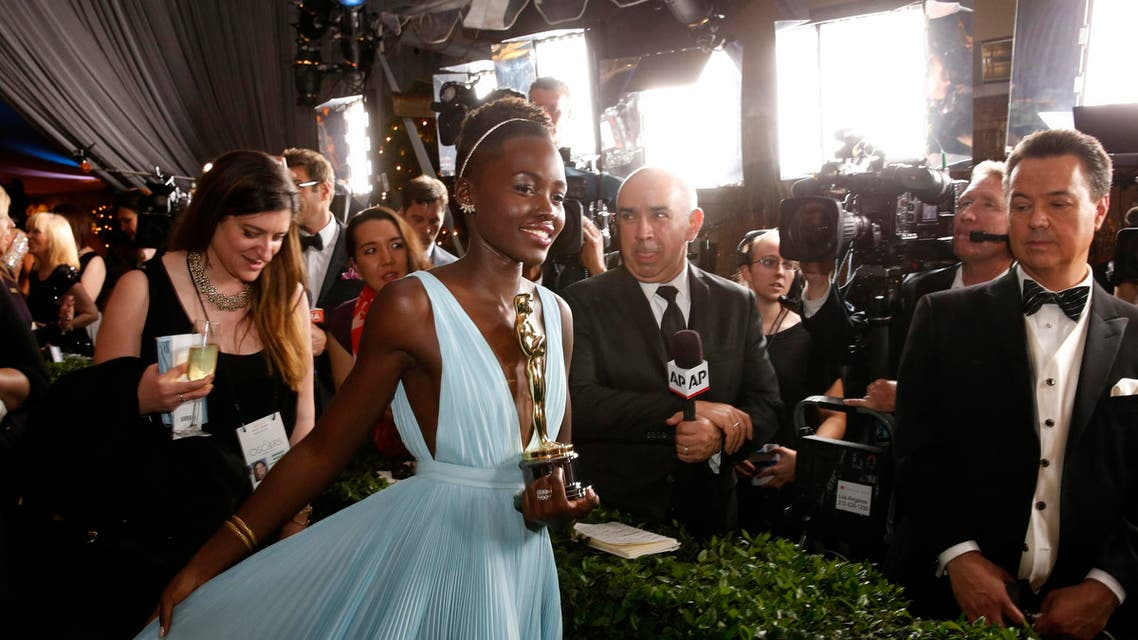 Lupita Nyong'o walks with her award for best supporting actress for her role in the film '12 Years a Slave' at the Governors Ball for the 86th Academy Awards in Hollywood, California. (Reuters)