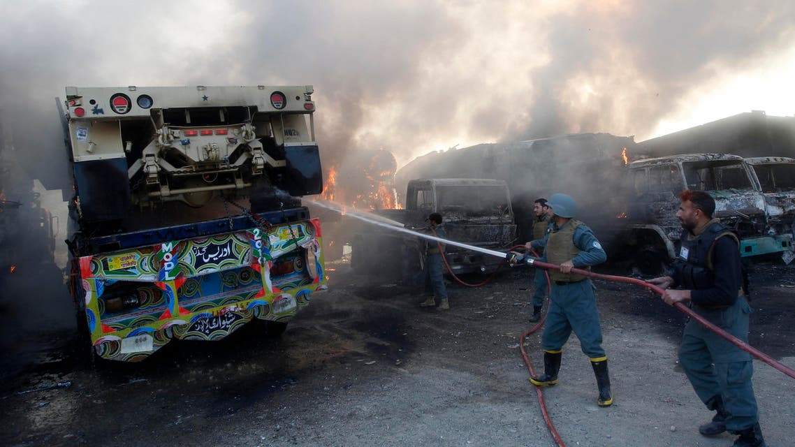 Afghan policemen extinguish burning NATO supply trucks after what police officials say was an attack by militants in the Torkham area near the Pakistani-Afghan border in Jalalabad Province December 18, 2013.