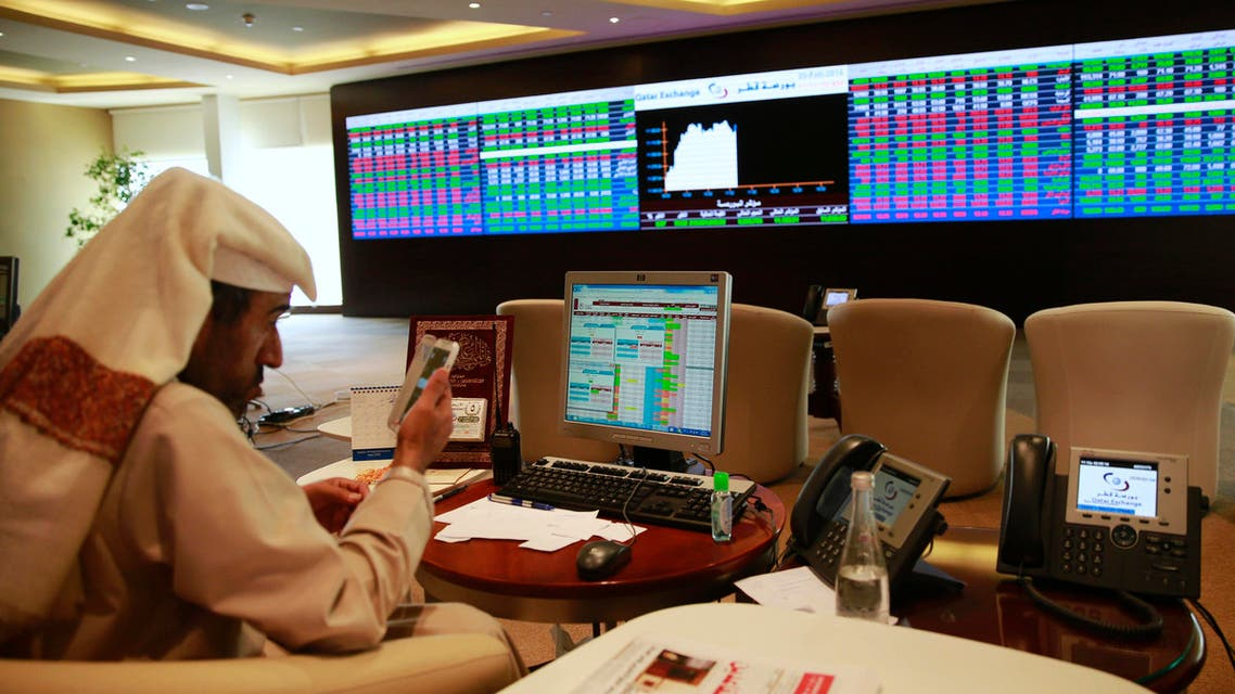 A trader uses his mobile phone behind his desk in front of the Qatar stock exchange board, in Doha February 4, 2014. (File photo: Reuters)
