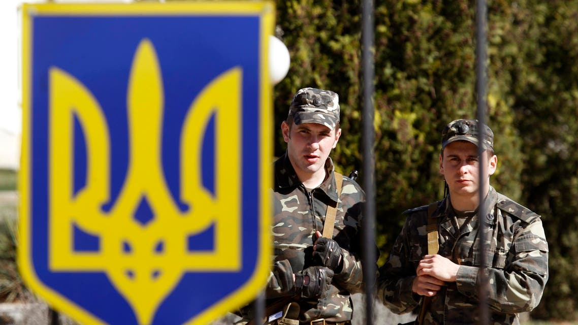 Ukrainian servicemen stand guard on the territory of their military unit located southwest of Crimea's capital. (Reuters)