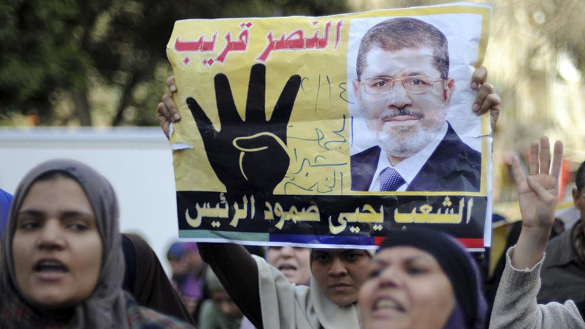 """Supporters of Muslim Brotherhood and ousted Egyptian President Mohamed Mursi shout slogans against the military and the interior ministry as they gesture with the sign """"Rabaa"""", or """"Four"""", during a protest around Ain Shams square in east Cairo February 14, 2014. reuters"""
