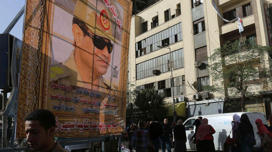 People walk past a huge banner for Egypt's army chief, Field Marshal Abdel Fattah al-Sisi in downtown Cairo, March 4, 2014. (Reuters)