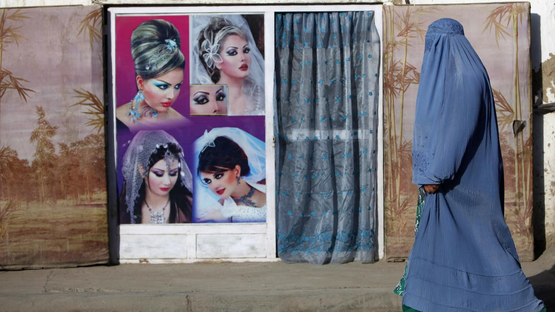 An Afghan woman in a burqa walks past a beauty saloon shop in Kabul September 11, 2013.