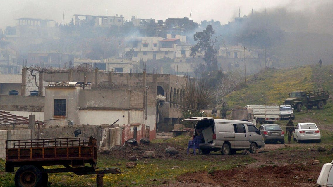 A handout picture released by the official Syrian Arab News Agency (SANA) shows smoke billowing from houses in the town of Zara, in the province of Homs, on March 8, 2014. (AFP)
