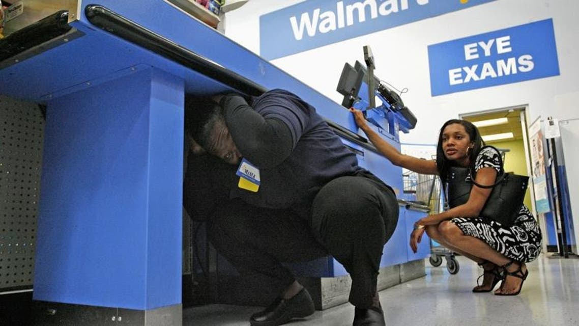 """Walmart Employee Velma Madden (L) crouches under a checkout stand to practice the drop, cover, and hold on technique during the """"Great ShakeOut"""" earthquake drill at Walmart in Torrance, California October 17, 2013."""