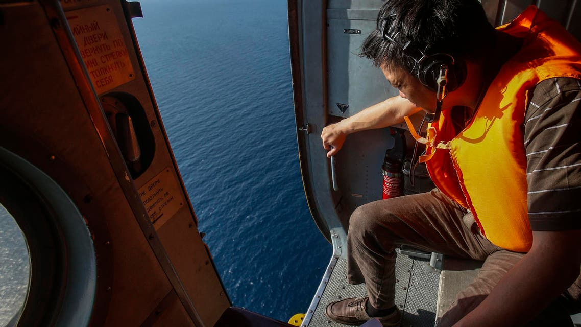 An officer looks out of a helicopter during a mission to find the Malaysia Airlines flight MH370 that disappeared from radar screens in the early hours of Saturday, near Tho Chu island March 10, 2014. (Reuters)