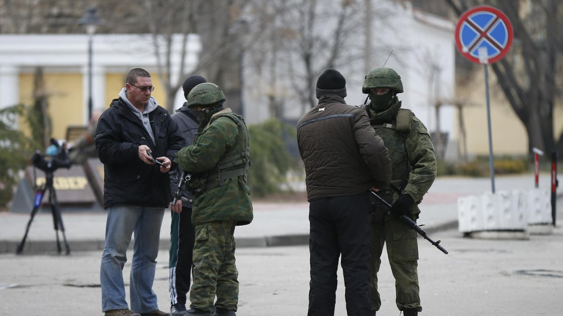 Armed men check journalists' documents around the regional parliament building in the Crimean city of Simferopol on March 1, 2014. (File photo: Reuters)