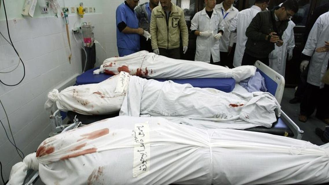 Palestinian medics check the shrouded bodies of three killed militants from the Islamic Jihad's armed wing, the Al-Quds Brigades, at the hospital morgue before their burial in Khan Yunis following an Israeli air strike in the southern Gaza Strip, on March 11, 2014.