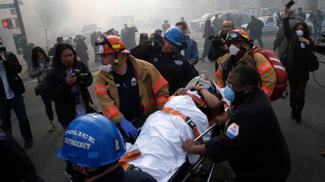 A victim is evacuated by emergency personal near an apparent building explosion fire and collapse in the Harlem section of New York City, March 12, 2014.
