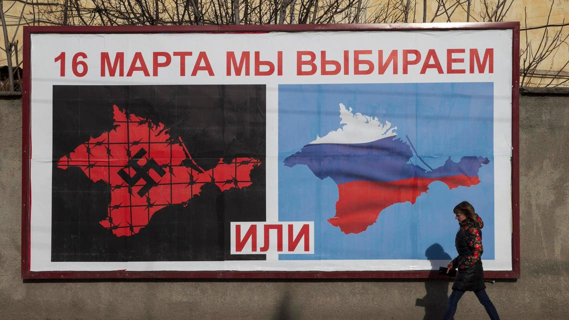 A woman walking by a poster calling people to vote in the upcoming referendum, in the Crimean port city of Sevastopol March 10, 2014. reut