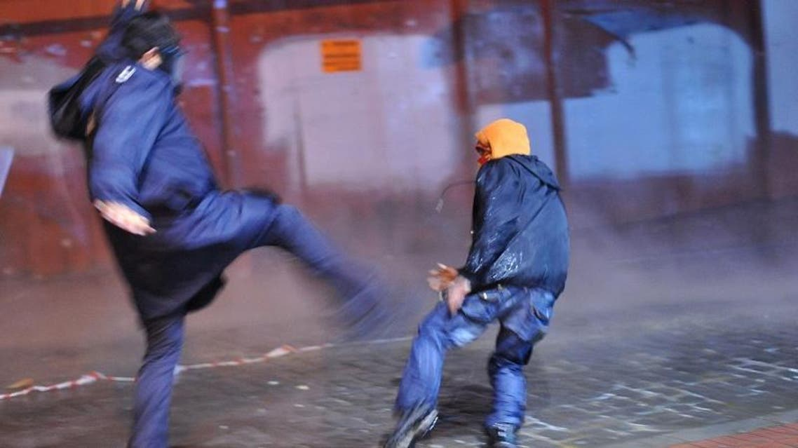 A riot police tries to kick a protestor during clashes at Istiklal avenue on March 11, 2014 in istanbul.