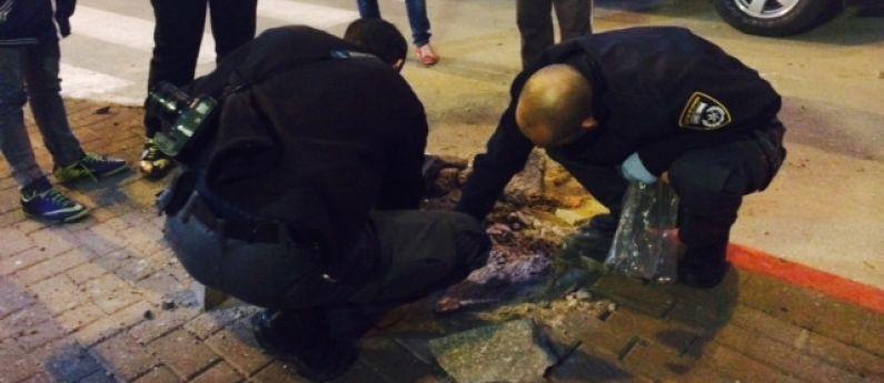 خبراء المتفجرات اسرائيليون يجمعون شظايا صاروخ اطلق من غزة