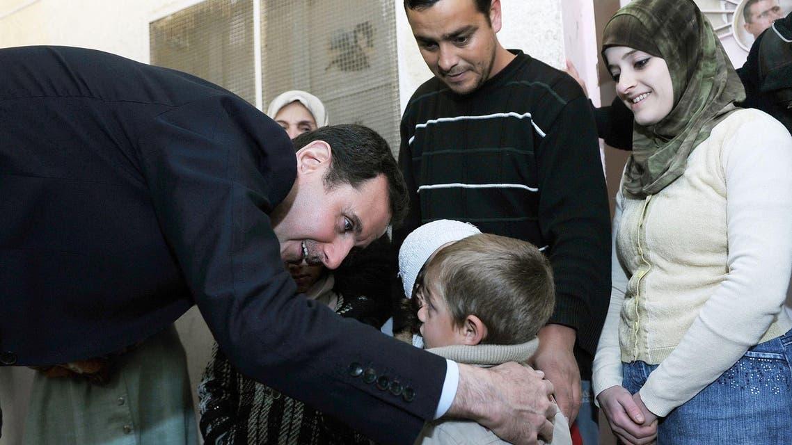 بشار الأسد يعانق الأطفال في مركز نازحين خارج دمشق