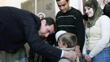الأسد يعانق الأطفال في مركز نازحين خارج دمشق