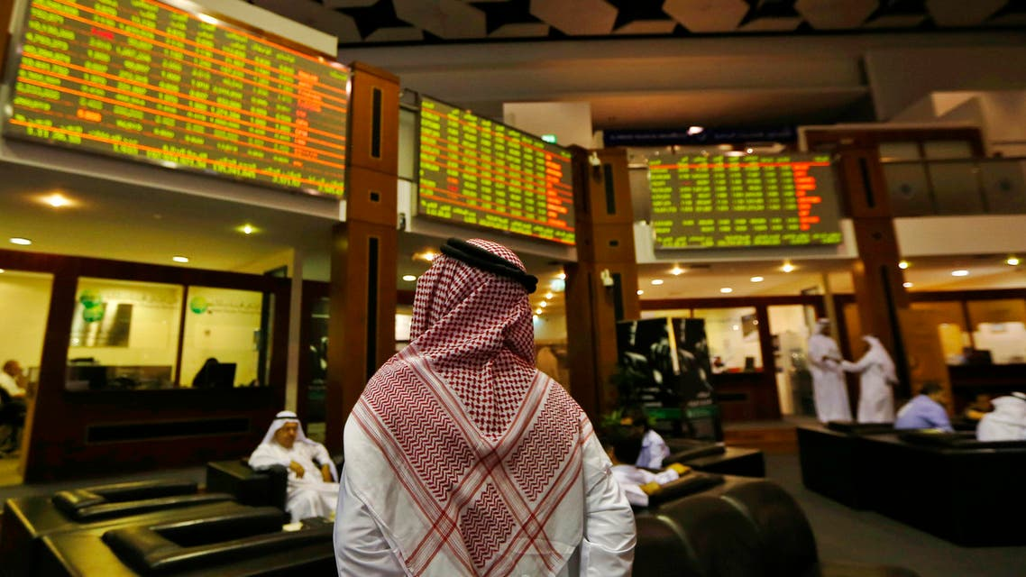 An investor looks up at screens displaying stock information at the Dubai Financial Market, June 17, 2013. (Reuters)