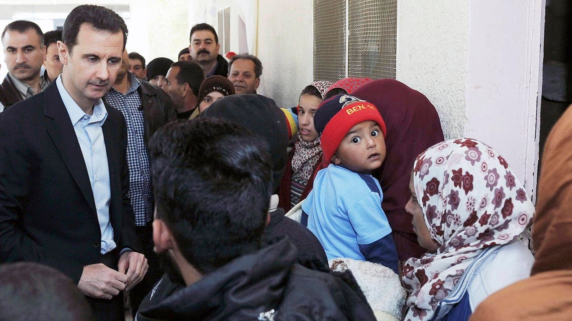 Syria's President Bashar al-Assad speaks with children during his visit to displaced Syrians in the town of Adra in the Damascus countryside March 12, 2014. (Reuters)