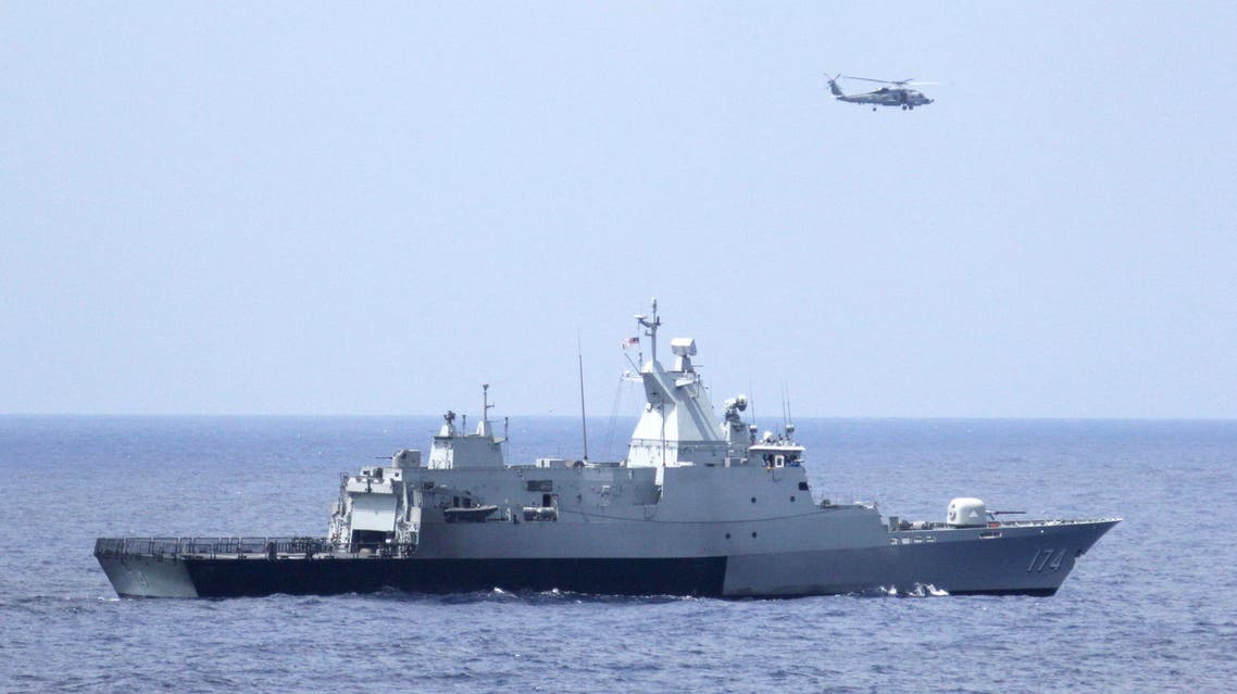 A Malaysian navy warship and a U.S. Navy helicopter conduct a coordinated air and sea search for a missing Malaysian Airlines jet in the Gulf of Thailand March 12, 2014. (Reuters)