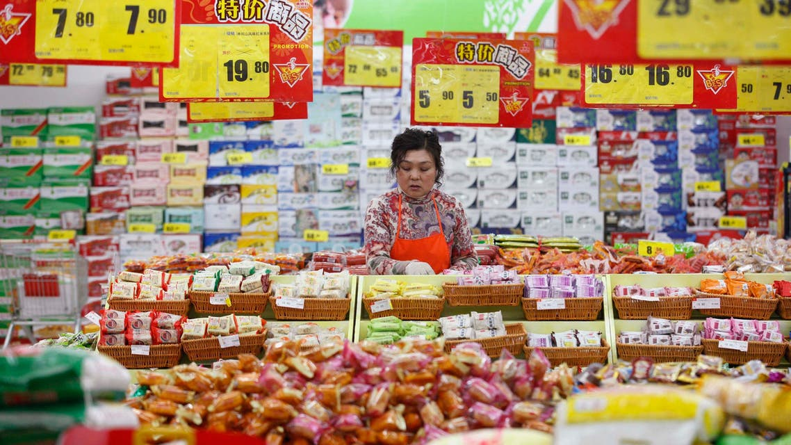 An employee arranges stock under price tags at a supermarket in Huaibei, Anhui province in China, March 9, 2014.
