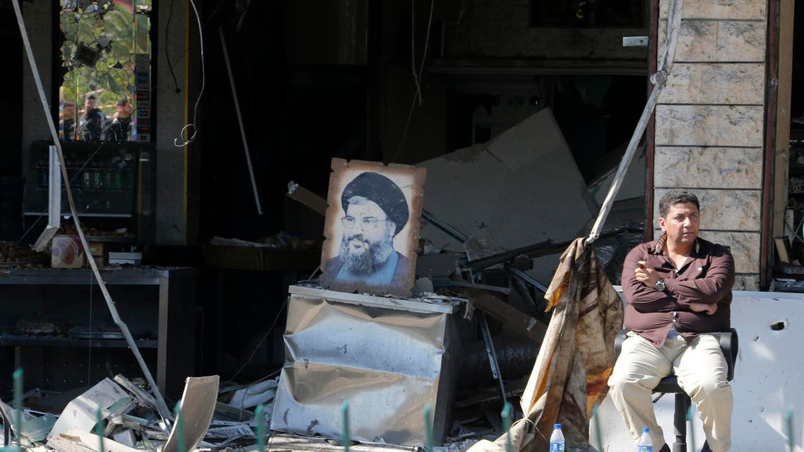 A man holds a cigar while sitting near a picture of Lebanon's Hezbollah leader Sayyed Hassan Nasrallah, in front of a damaged shop at the site of an explosion in the southern suburbs of Beirut Feb. 19, 2014. (Reuters)
