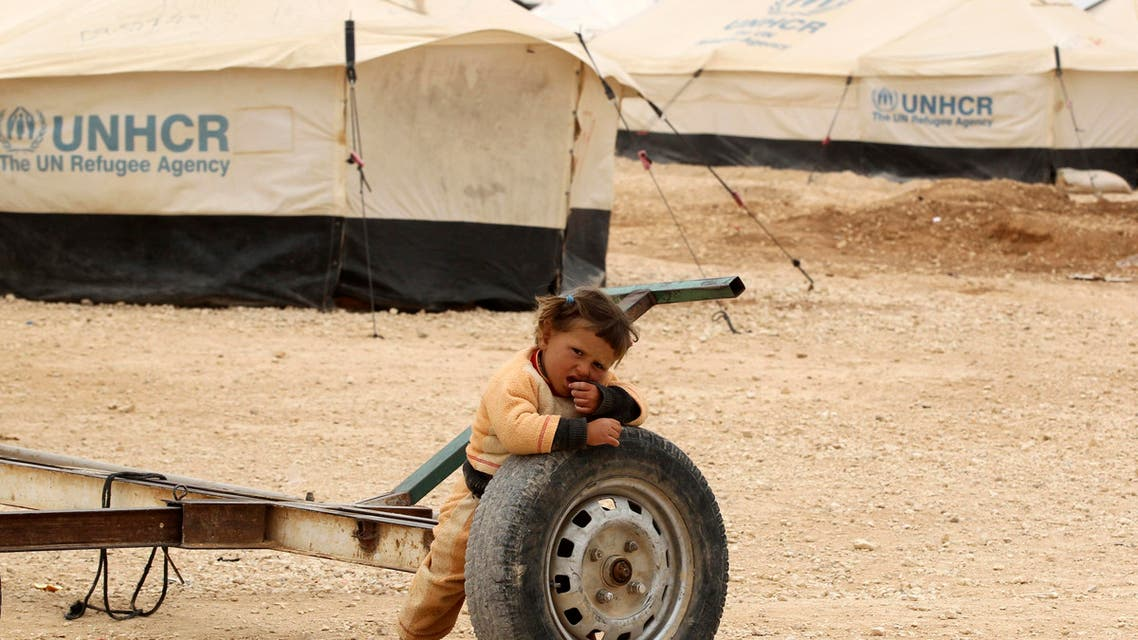 A Syrian refugee child plays at Alzaatri Syrian refugee camp in the Jordanian city of Mafraq, near the border with Syria