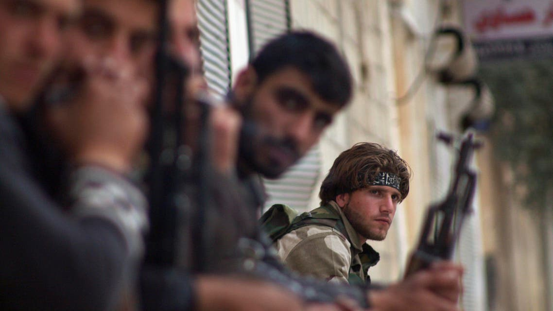 A Free Syrian Army sits with his fellow fighters in the town of Morek in Hama province March 11, 2014. (Reuters)