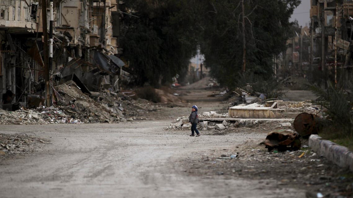 A child walks along a damaged street covered with debris in Deir al-Zor, eastern Syria February 3, 2014. (Reuters)
