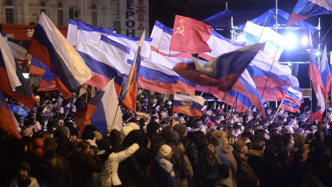 Pro-Russian Crimeans wave Russian flags as they gather to celebrate in Simferopol's Lenin Square on March 16, 2014. (AFP)
