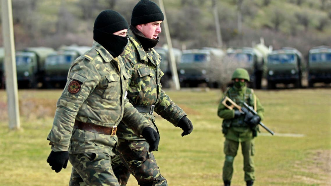 Ukrainian servicemen walk past an armed man, believed to be Russian, at the Ukrainian military base in Perevalnoye, outside Simferopol March 17, 2014. (Reuters)