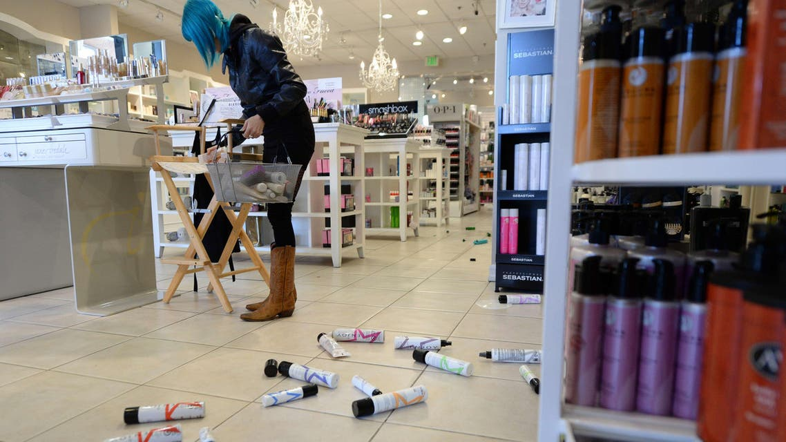 Employee Paula Anania cleans up hair care products that were knocked off the shelf in a beauty supply store in the Encino area of Los Angeles after a 4.4 earthquake jolted the area March 17, 2014. (AFP)