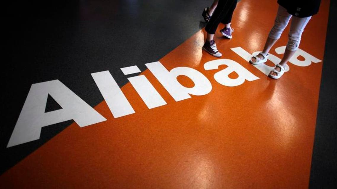 Employees stand on a logo of Alibaba (China) Technology Co. Ltd during a media tour organised by government officials at its headquarters on the outskirts of Hangzhou, Zhejiang province June 20, 2012.