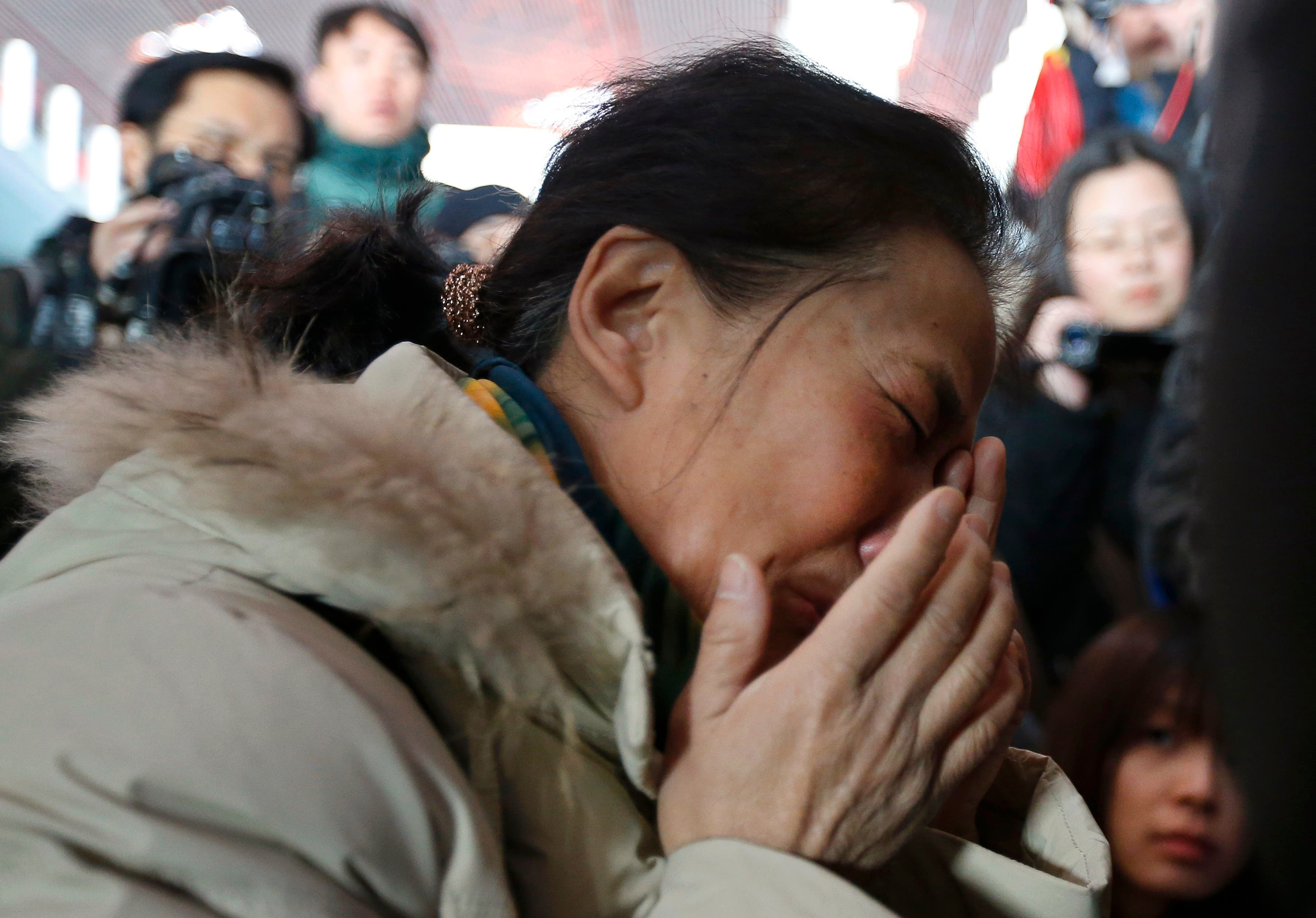 A relative of a passenger onboard Malaysia Airlines flight MH370 cries, surrounded by journalists, at the Beijing Capital International Airport in Beijing March 8, 2014 reuters