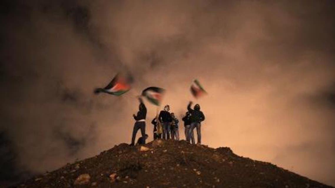 Palestinians wave their national flag as they await the release of Palestinian prisoners in Jerusalem on Dec. 31, 2013. (AFP)