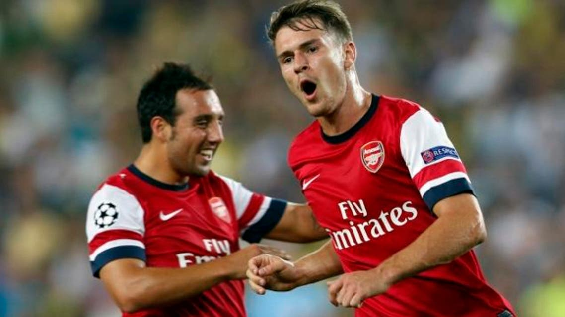 """Arsenal midfielder Aaron Ramsey celebrates with teammate Santi Cazorla after scoring against Fenerbahce in their Champions League playoff first leg, August 21(Photo : Reuters) """""""