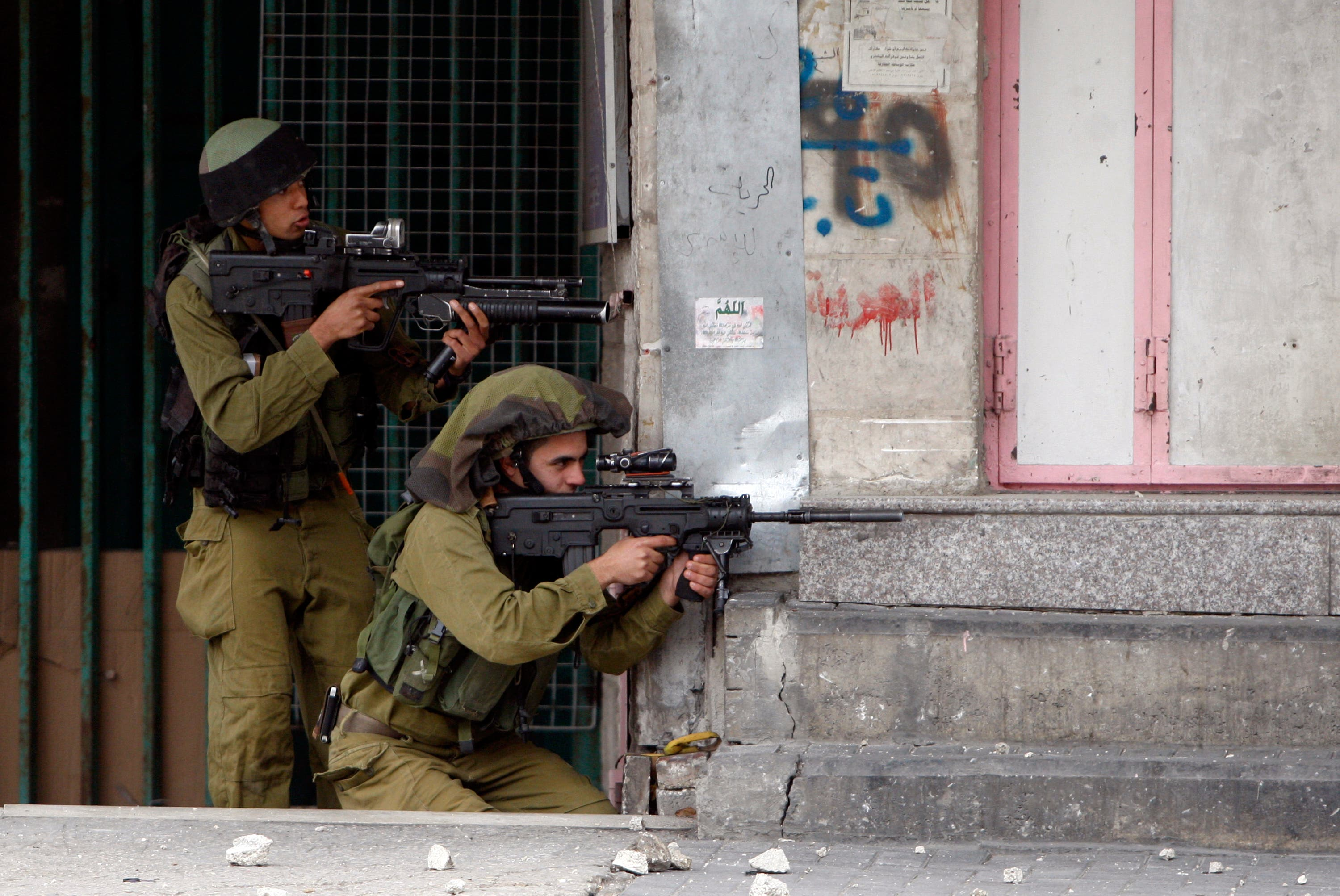 Israeli soldiers take position during clashes with stone-throwing Palestinians that followed a rally to support President Mahmoud Abbas in the West Bank city of Hebron March 17, 2014. reuters