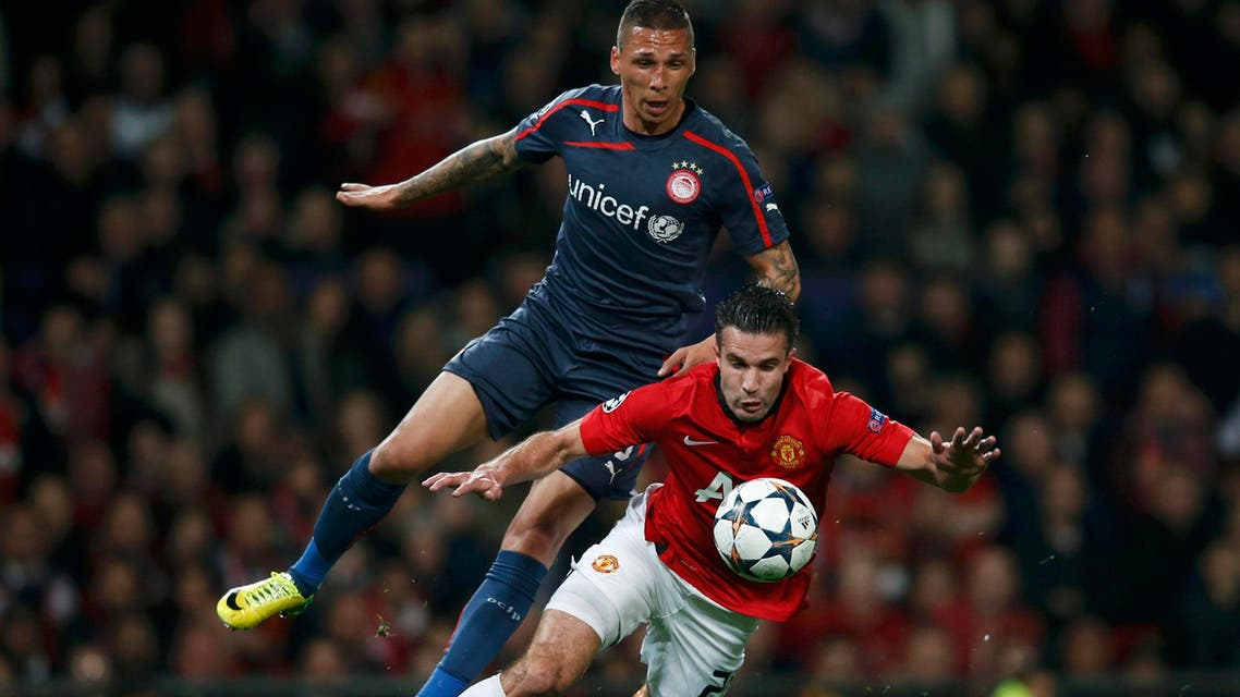 Manchester United's Robin van Persie (front) is fouled for penalty from Olympiakos' Jose Holebas during their Champions League soccer match at Old Trafford in Manchester, northern England, March 19, 2014. (Reuters)