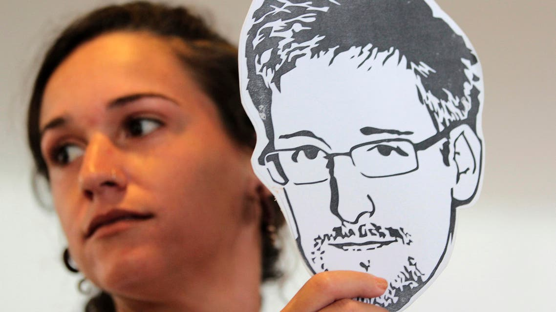 An activist from advocacy group Avaaz holds an illustration of former U.S. spy agency NSA contractor Edward Snowden during a delivery of a petition to the Itamaraty Palace in Brasilia February 13, 2014. reuters