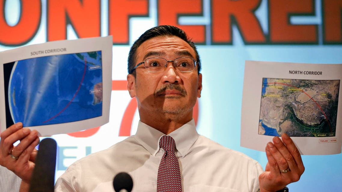Malaysia's acting Transport Minister Hishammuddin Hussein shows two maps with corridors of the last known possible location of the missing Malaysia Airlines MH370 plane. (Reuters)