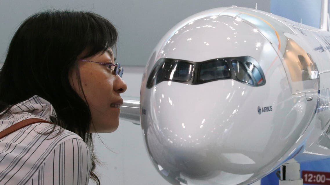 A visitor looks at a miniature Airbus A350 passenger aircraft at Aviation Expo China 2013 in Beijing. Reuters