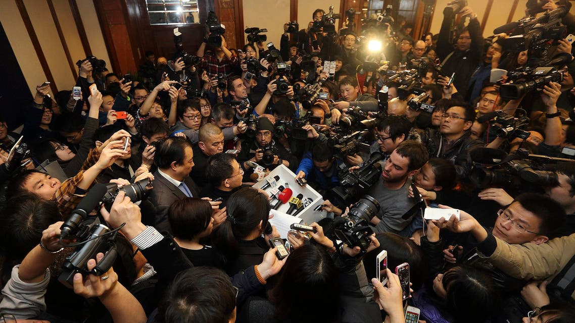 Media scrum: A Malaysia Airlines spokesman surrounded by journalists as he gives a briefing about flight MH370 on March 8, 2014. (Reuters)